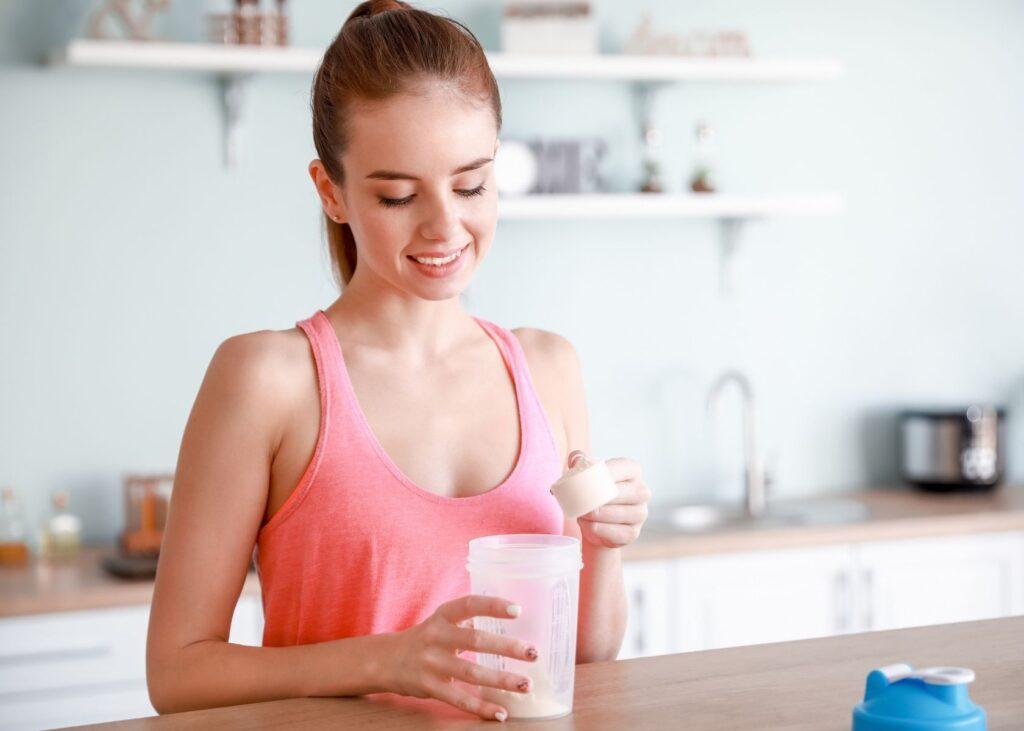 Woman mixes protein shake.