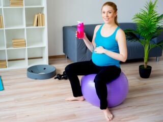 Pregnant woman sits on exercise ball and drinks Gatorade.