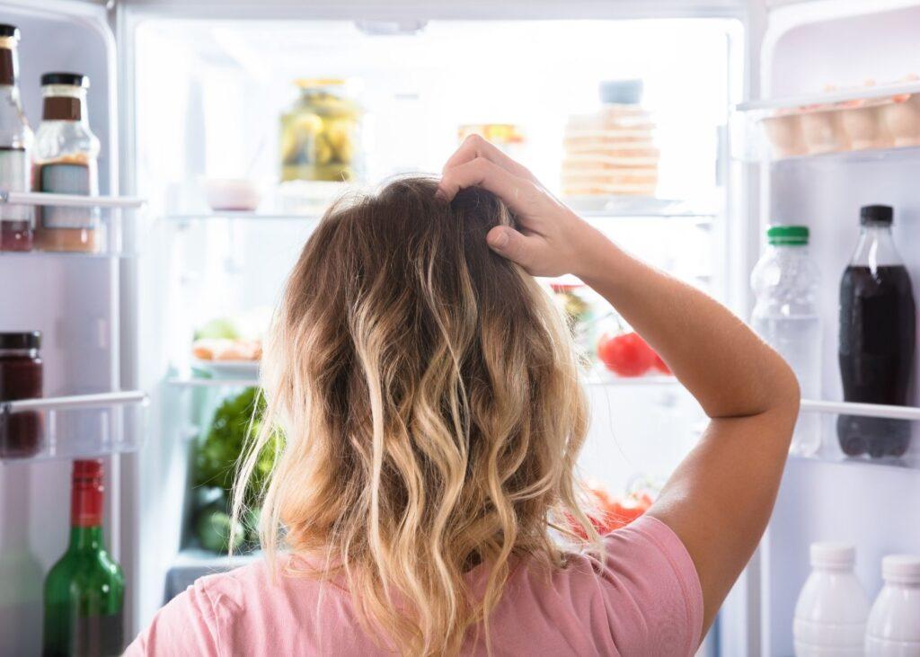 Pregnant women looks in fridge for sour cream.
