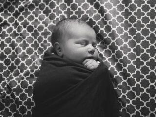 Newborn sleeping at night in black and white.