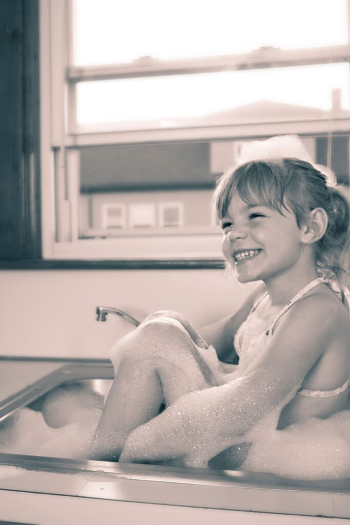 Little girl sits in a sink and smiles.