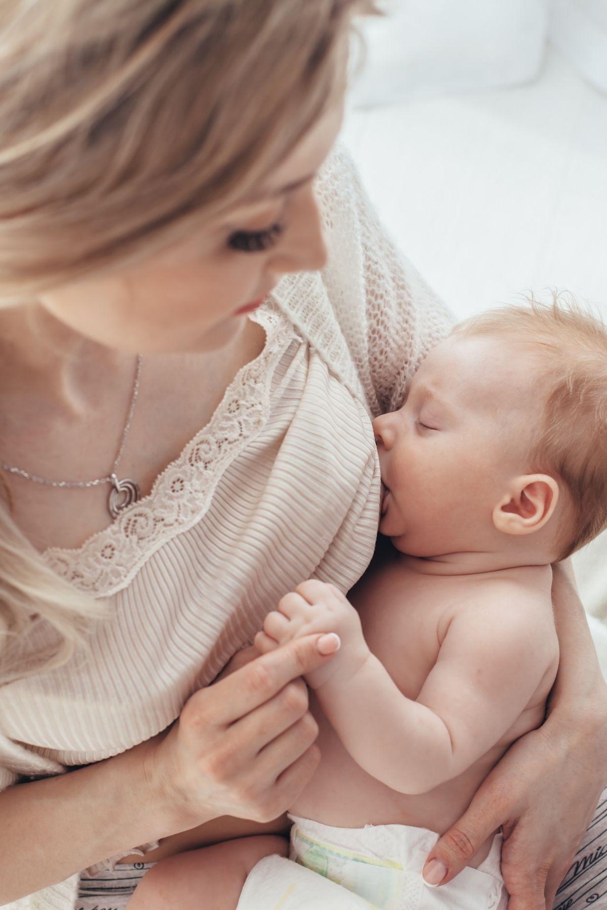 Mom breast feeds baby boy.