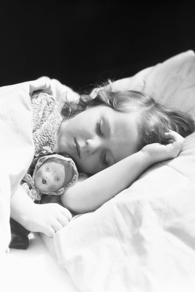 Old fashioned photo of girl sleeping with doll.