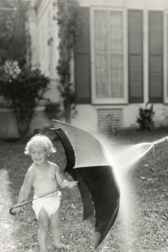 Old photo of girl holding umbrella while getting sprayed with hose.