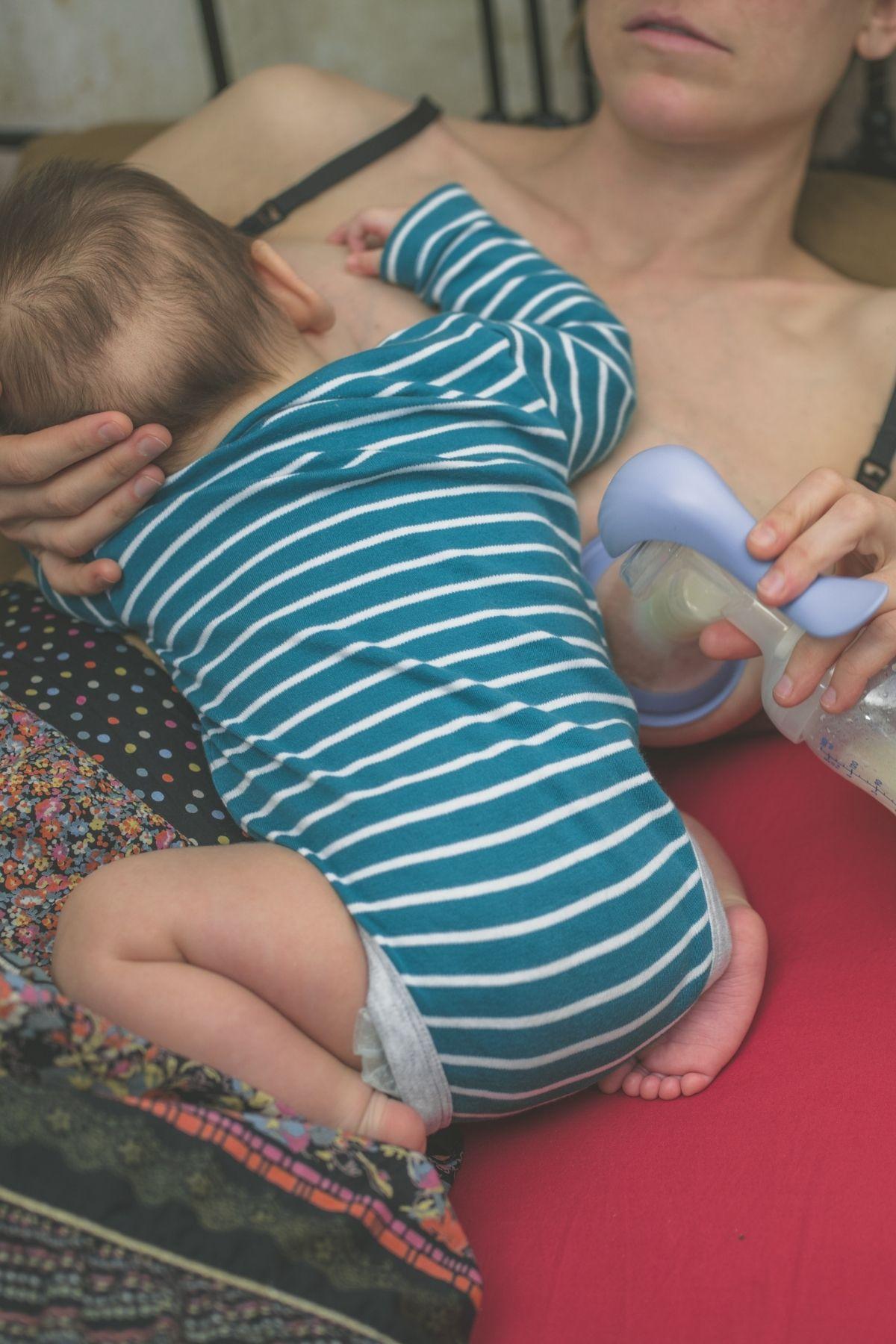 Woman uses handheld pump with breastfeeding baby.