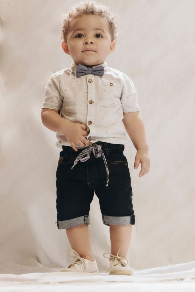 Baby boy with bow tie poses for picture.