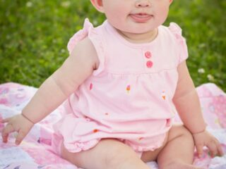 Baby girl sits outside on picnic blanket.
