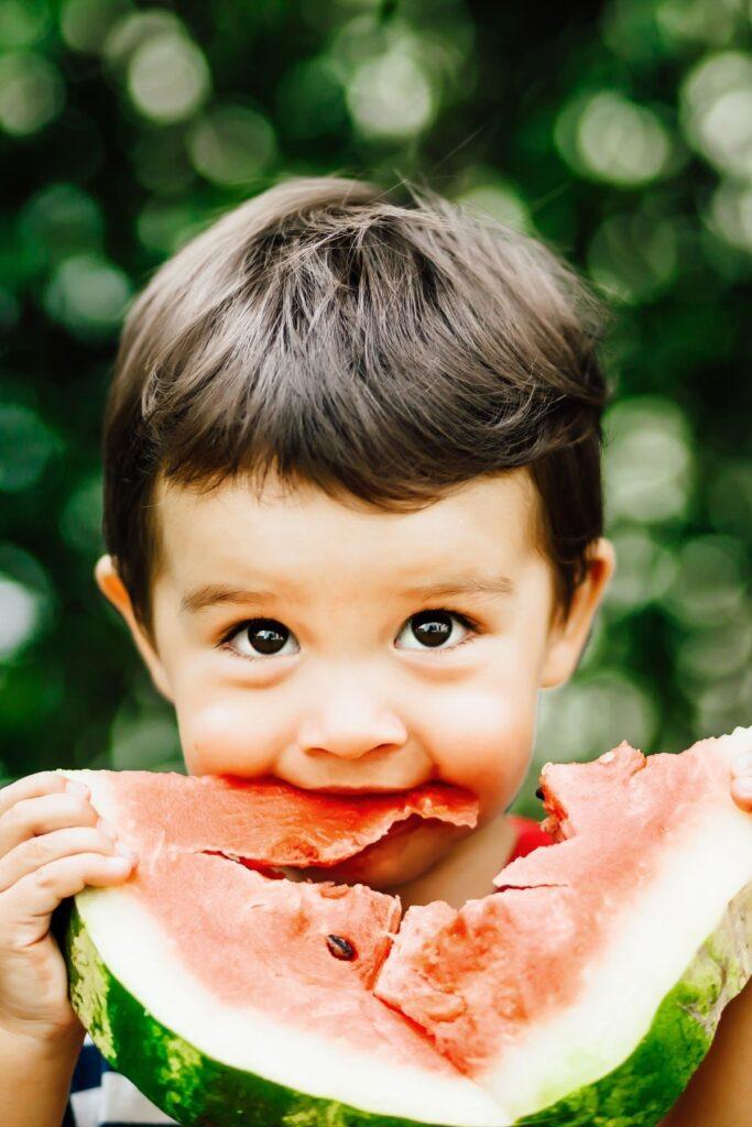 Little boy eats watermelon outside.