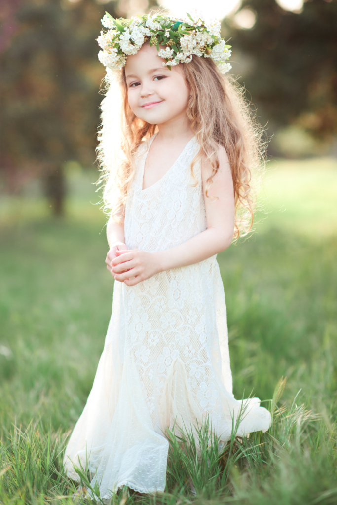 Little girl stands outside in white dress and flower crown.