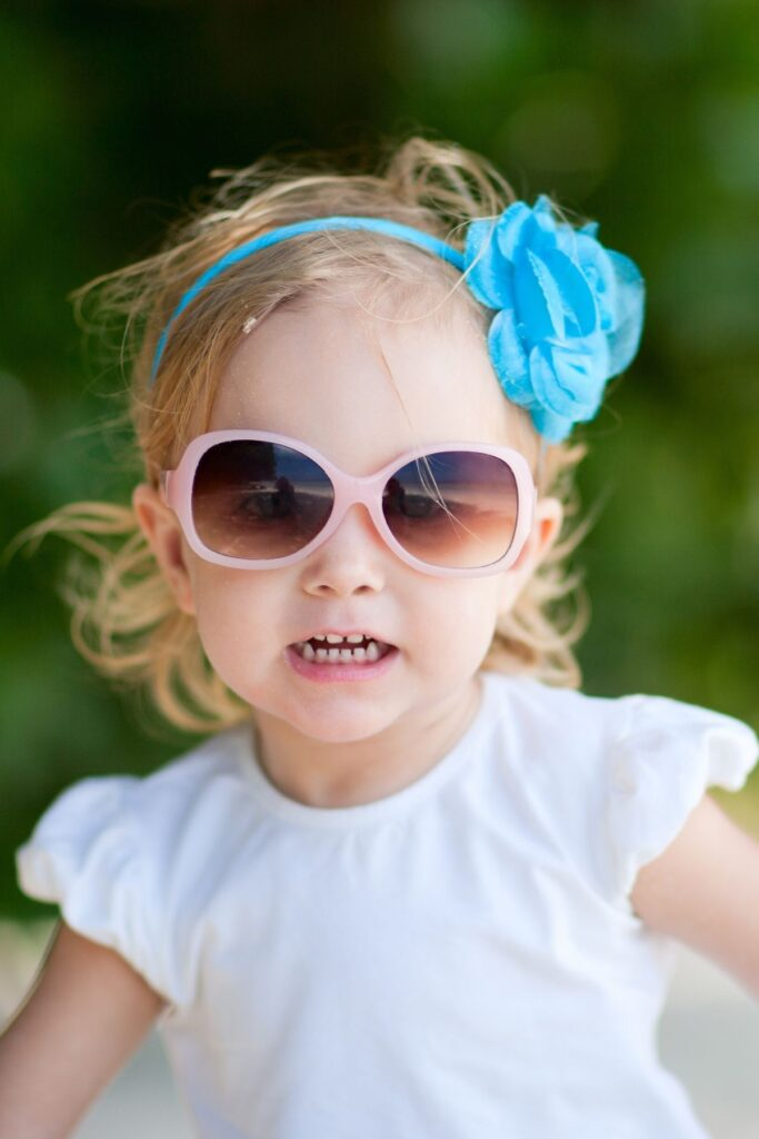 Toddler girl with blue hair bow and pink sunglasses.
