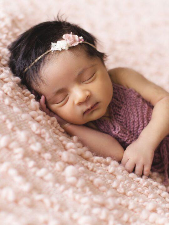 Baby girl sleeps on pink blanket.