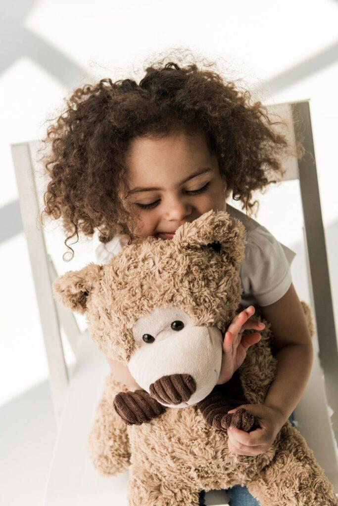 Girl with curly brown hair hugs teddy bear.
