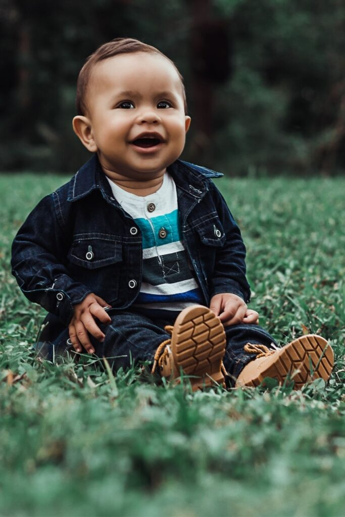 Baby boy in denim jacket and boots sits on grass.