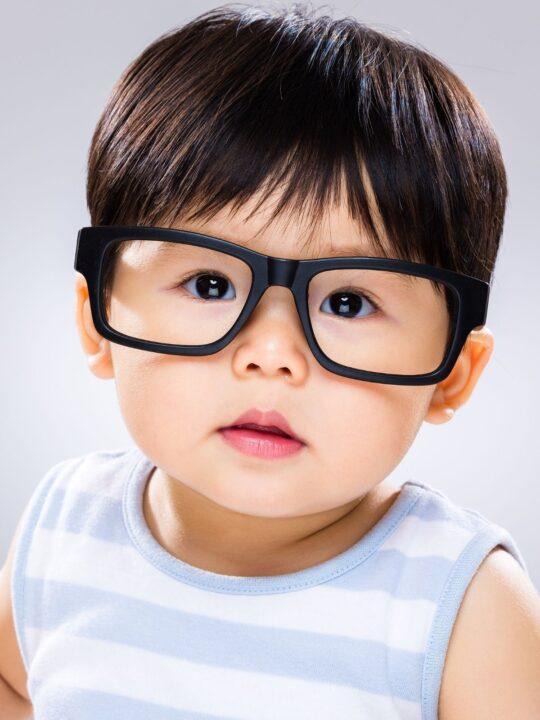 Baby boy wears black glasses.