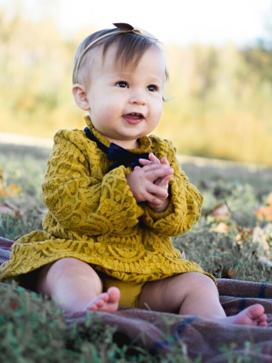 Baby girl sits outside in mustard dress.