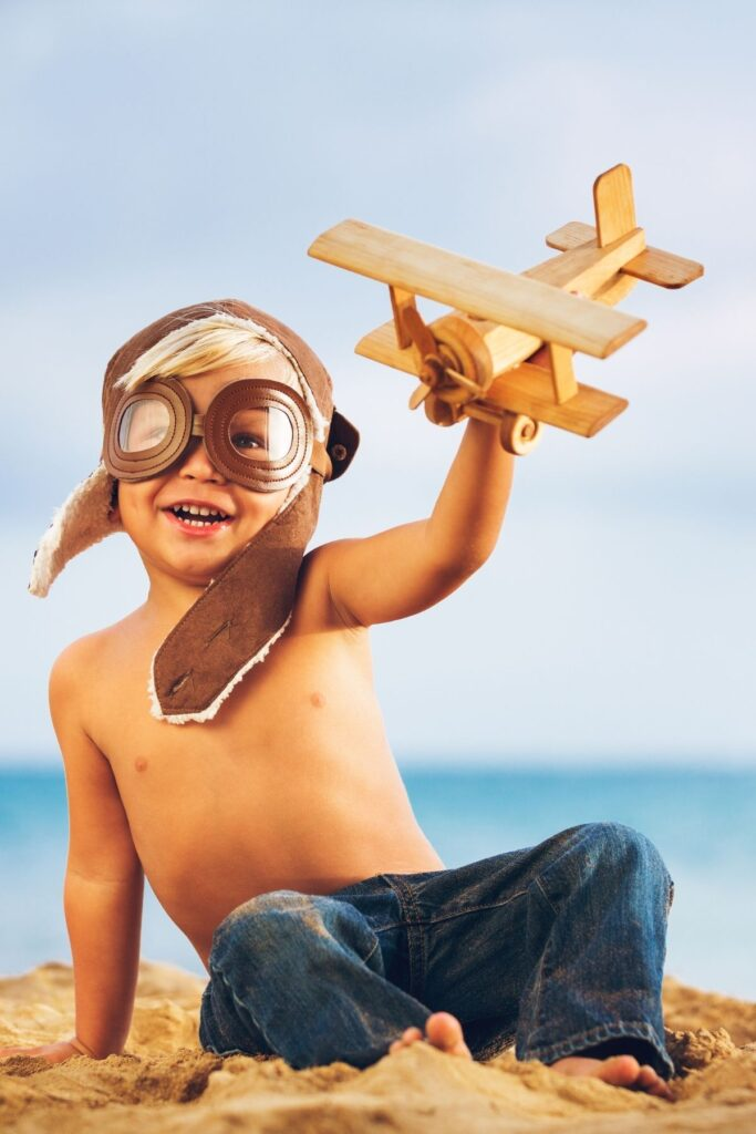 Boy plays with wooden airplane on beach.