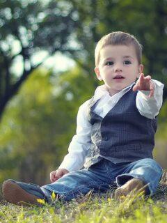 Little boy in vest sits outside.
