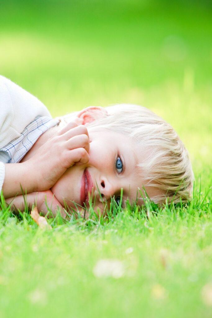 Little boy lies in grass.
