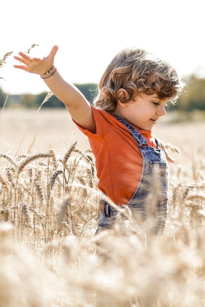 Little boy playing in wheat field.