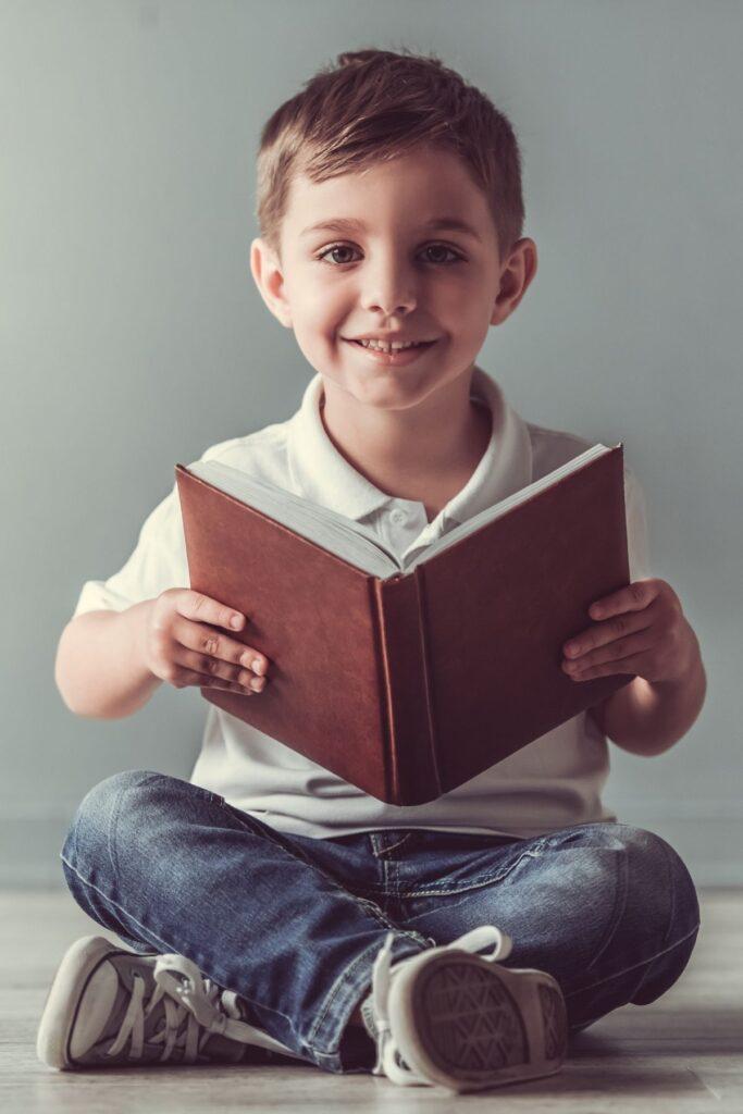 Little boy reads book on the floor.