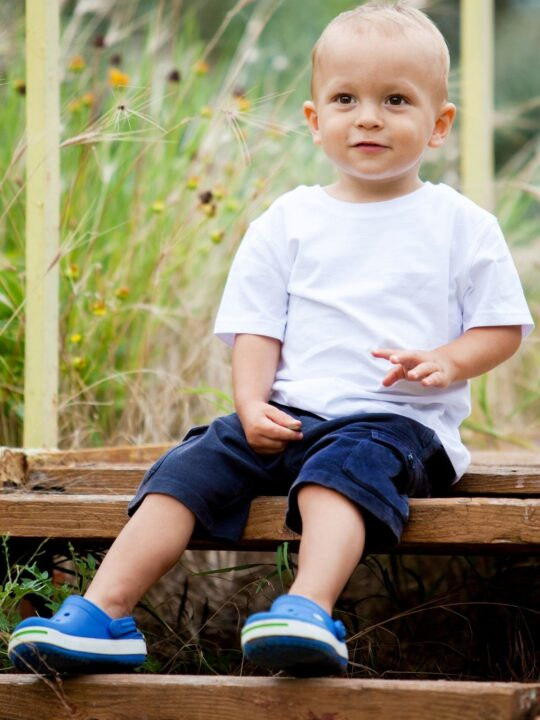 Little boy sits outside on wooden steps.