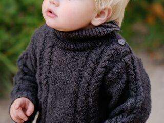 Little boy stands outside in black knit sweater.