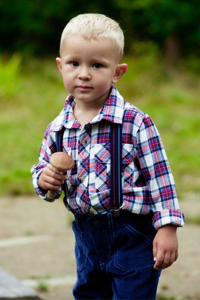 Little boy stands outside in suspenders.