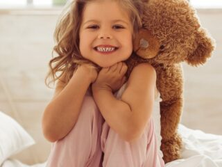 Little girl hugs teddy bear on bed.
