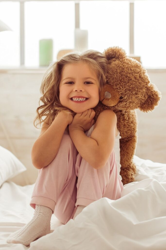 Little girl hugs teddy bear on bed.