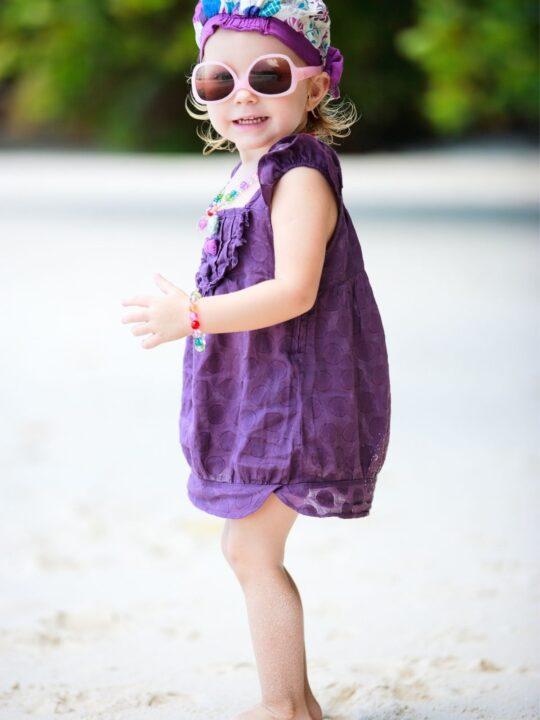 Little girl in sunglasses on the beach.