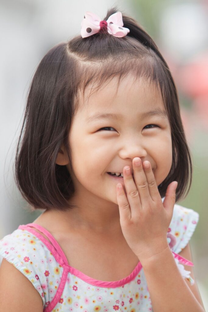 Little girl laughs with hand over mouth.