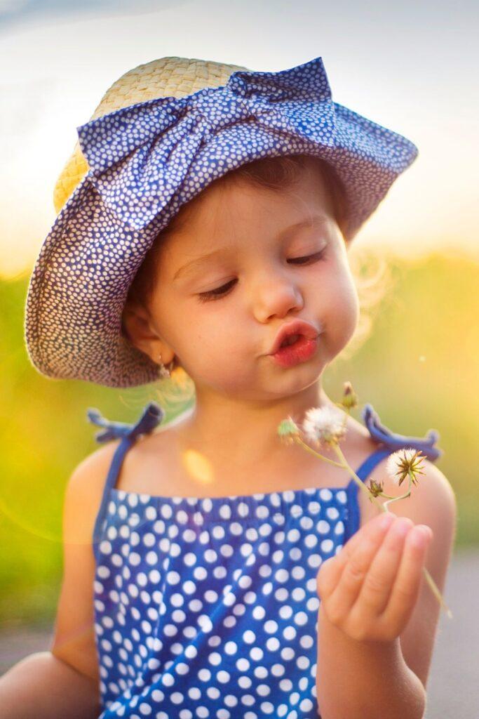 Little girl looks a wild flower in hand.