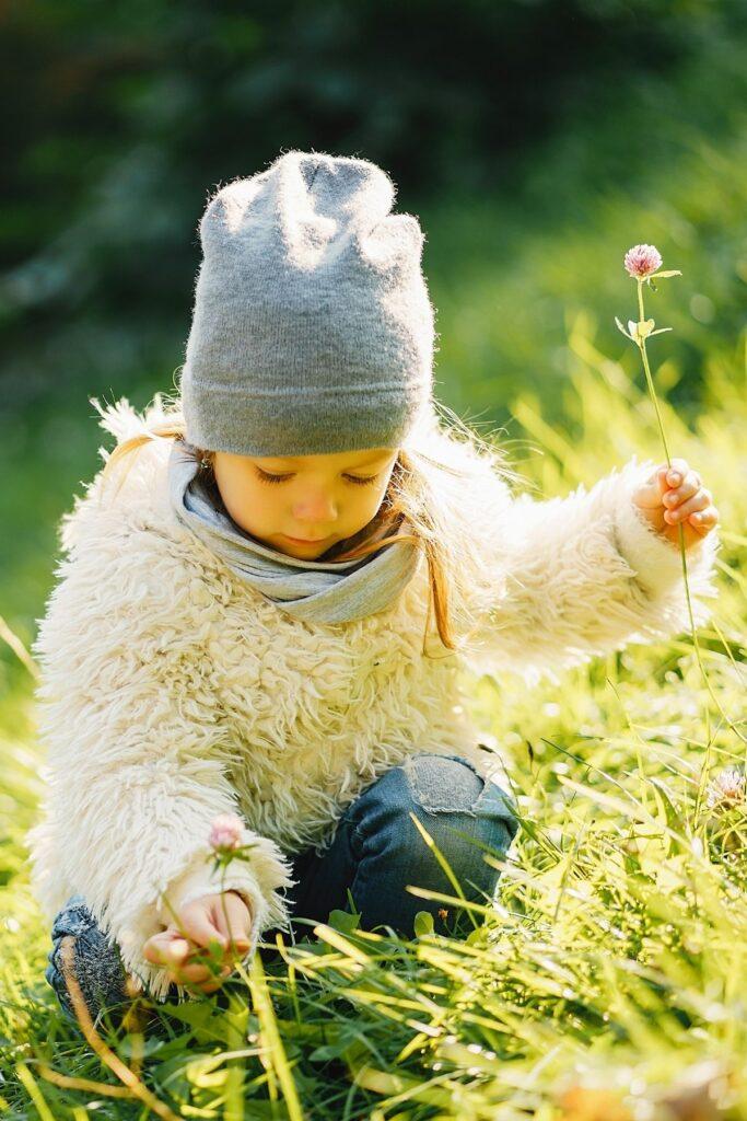 Little girl picks flowers in a meadow.