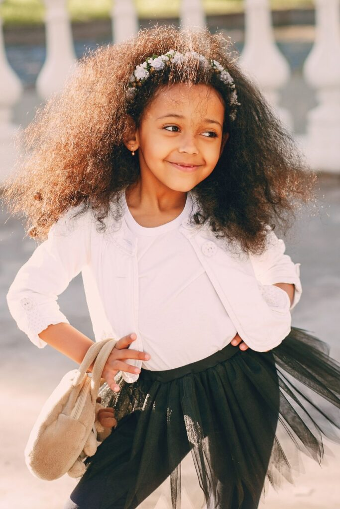 Little girl poses with hands on her hips.