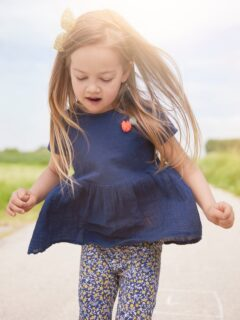 Little girl runs down country road.