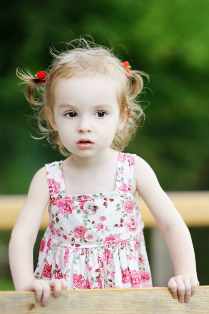 Little girl stands outside in floral spring dress.