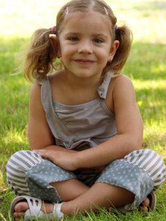 Little girl with pigtails sits on grass.