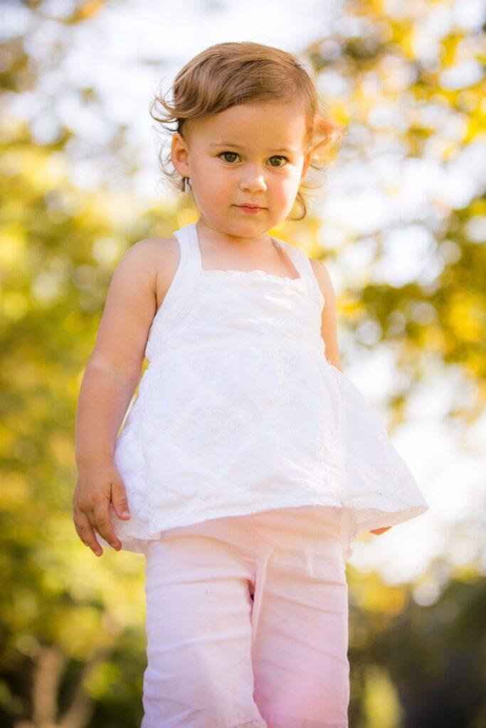 Toddler girl standing outside.