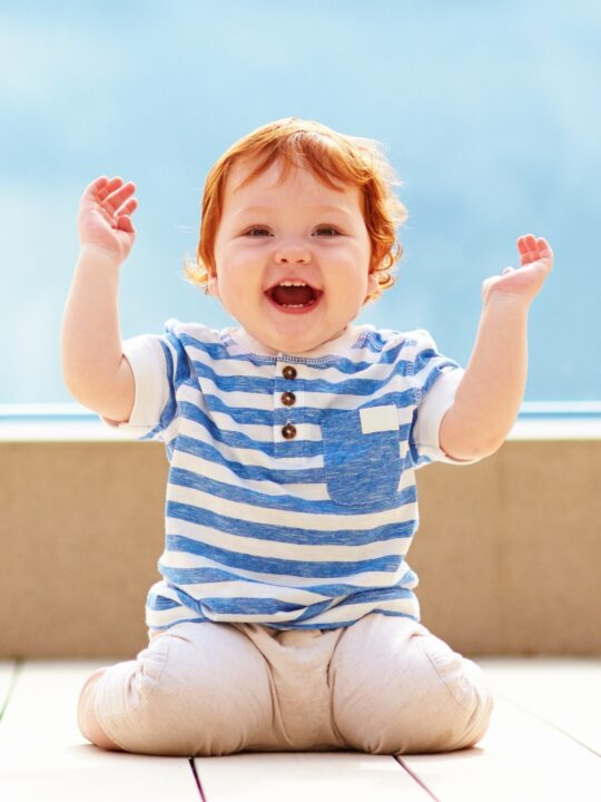 Happy baby boy raises hands in the air.