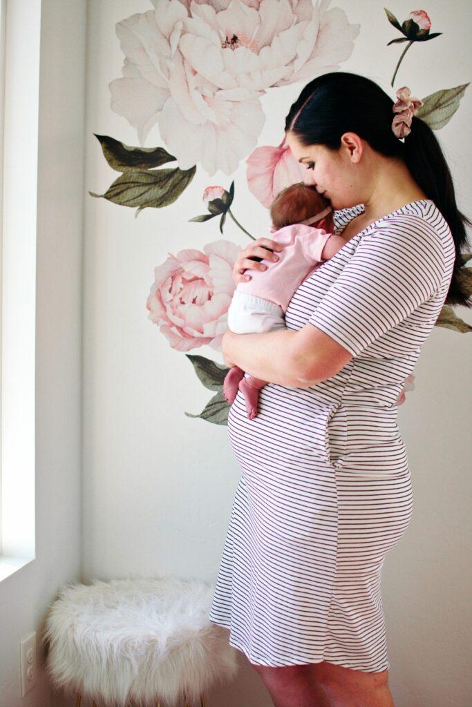 Mother holds newborn in nursery.