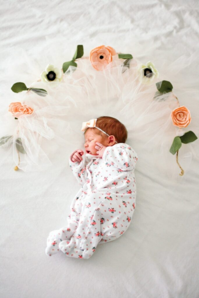 Newborn sleeps surrounded by flowers.