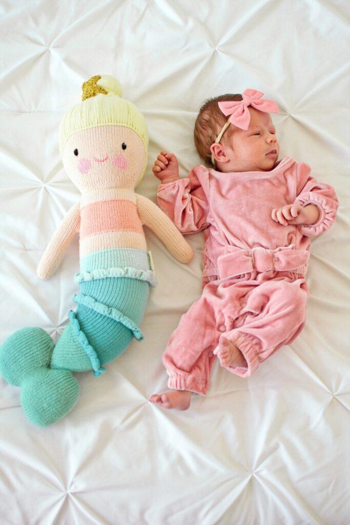 Newborn lies next to stuffed toy.