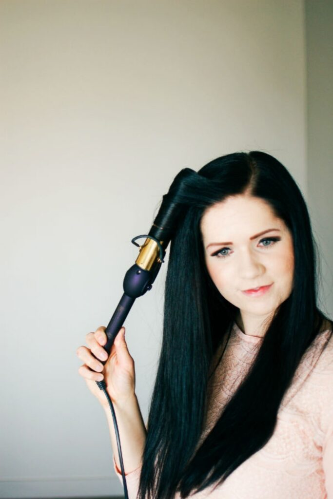 Woman curls hair with curling iron.