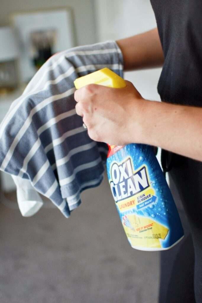 Woman sprays stain cleaner on shirt.