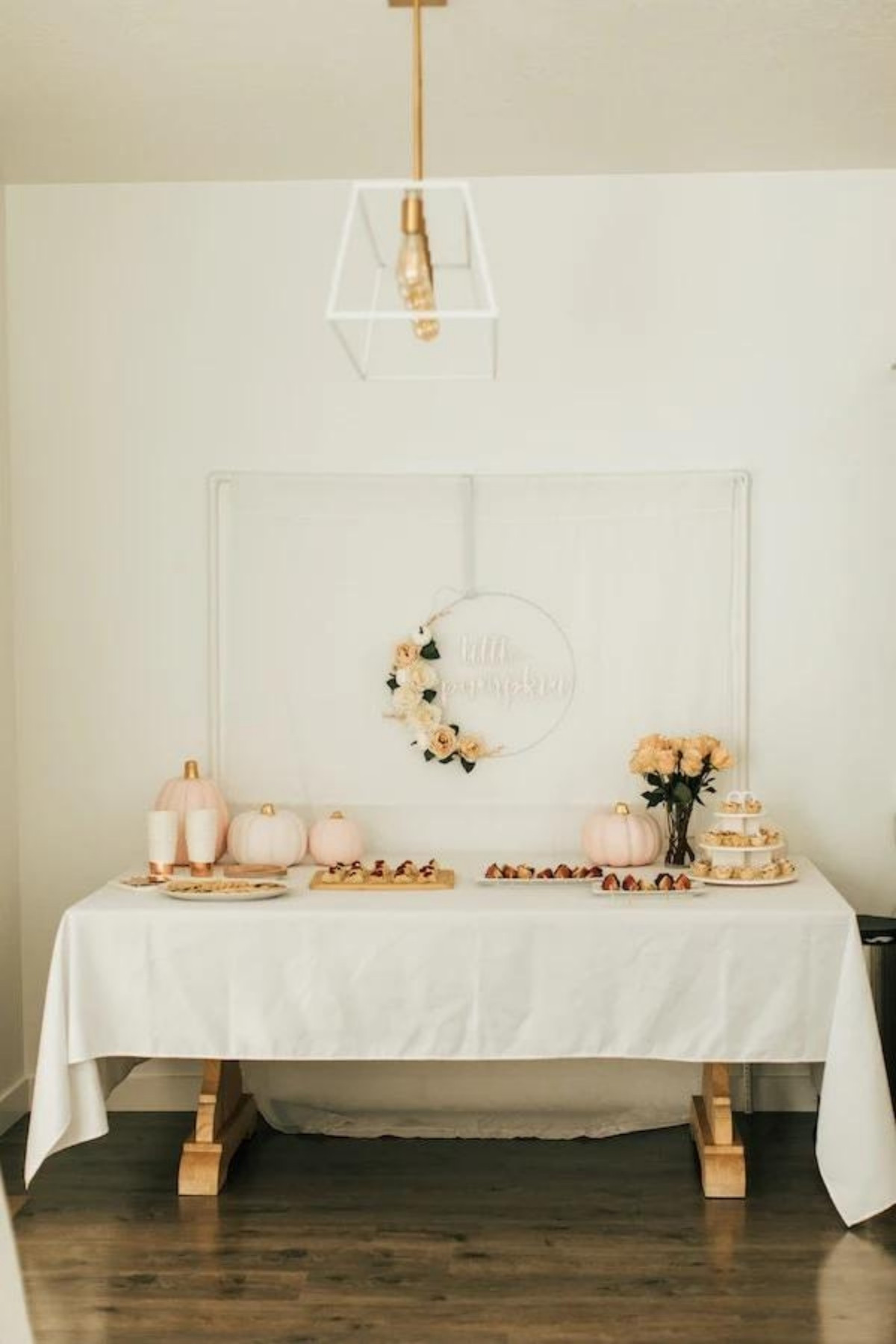 Party food table with trays of snacks, cups, pumpkins, flowers, and curtain backdrop.