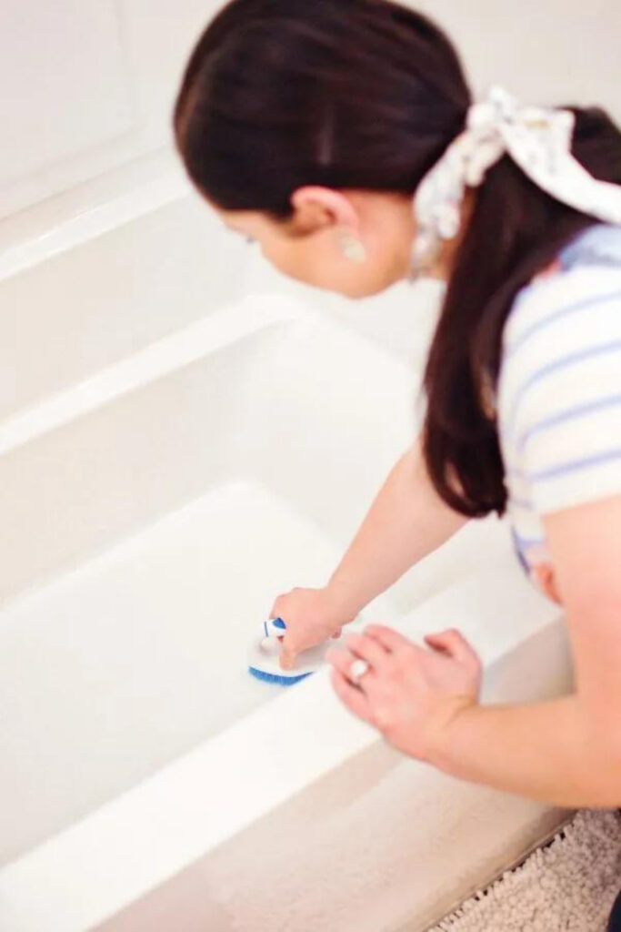 Woman cleans bathtub with brush.