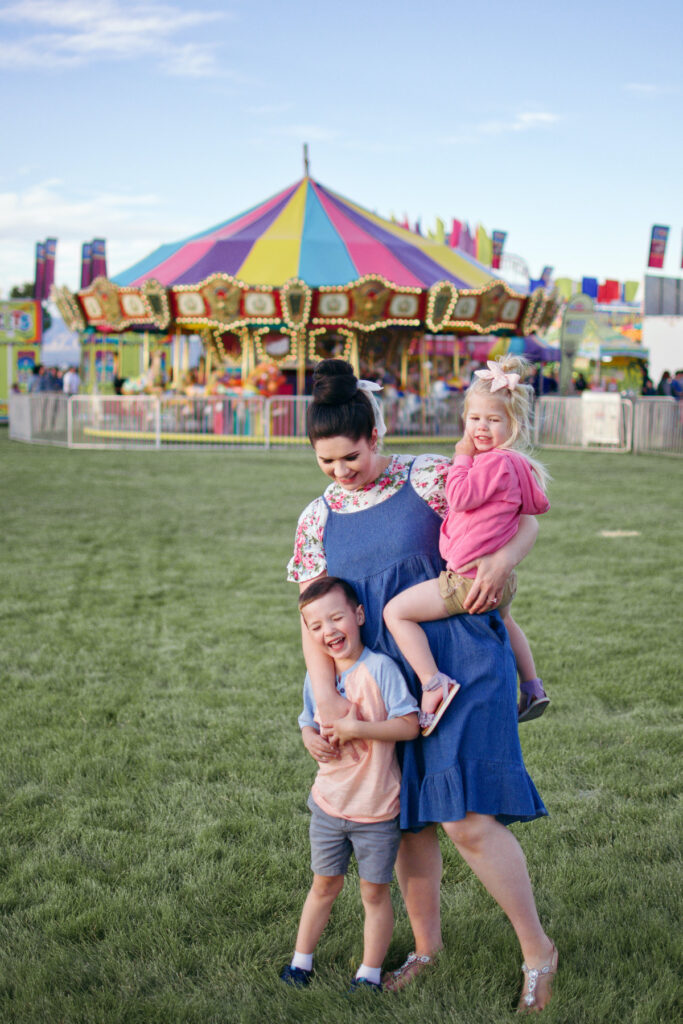 Mom stands with two kids in front of carnival.