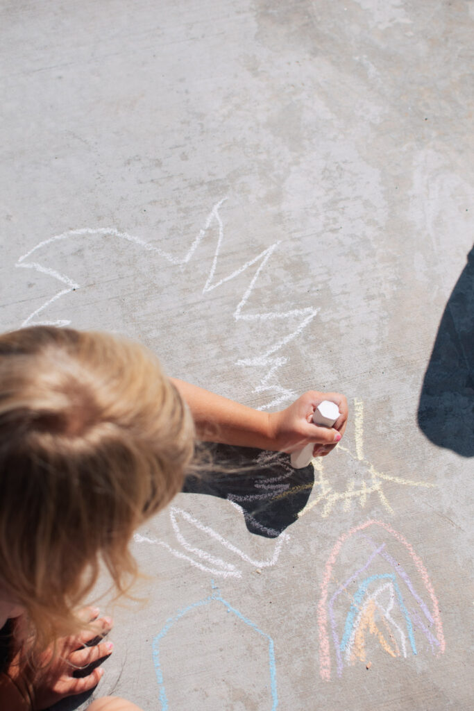 Little girl makes chalk drawing.