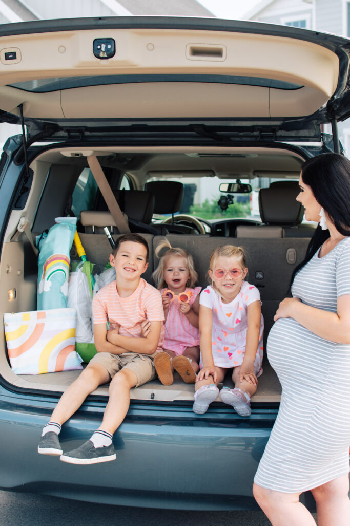 Three kids sit in trunk and smile while mom stands nearby.