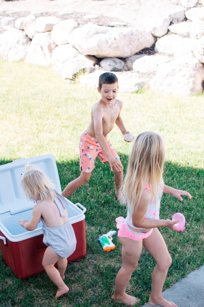 Three kids play with water balloons.